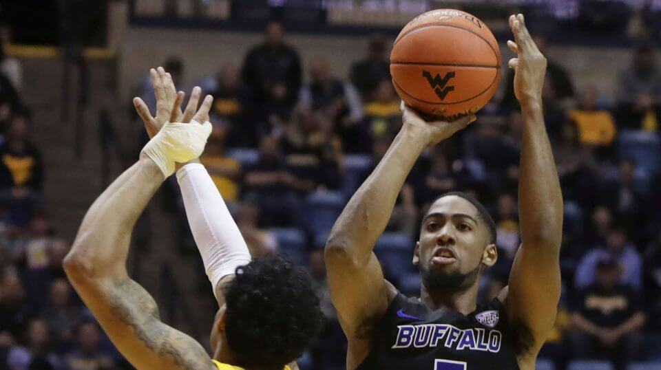 Buffalo guard C.J. Massinburg shoots while defended by West Virginia guard James Bolden during the first half Friday in Morgantown.