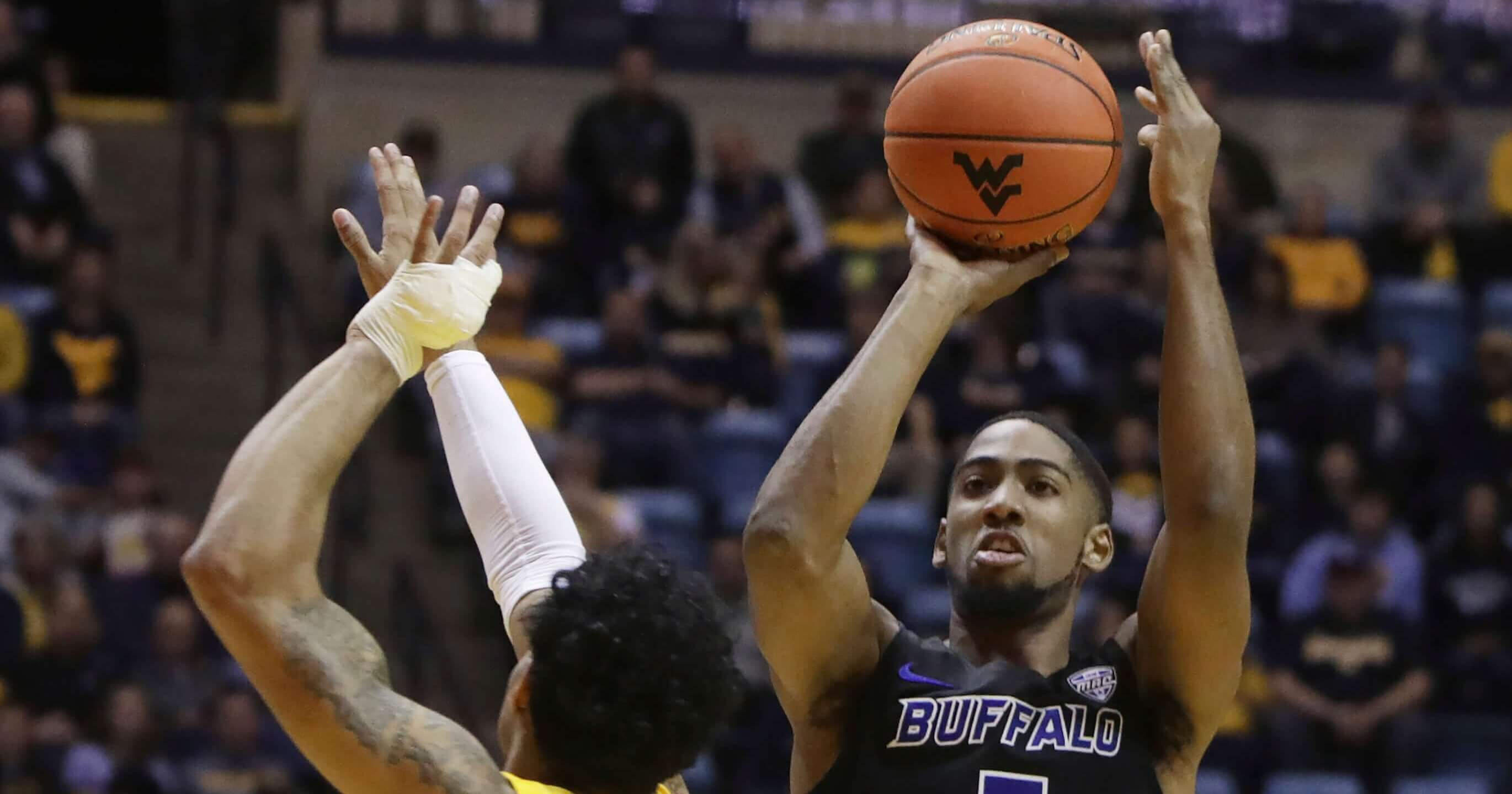 38df0ad9562 Buffalo guard C.J. Massinburg shoots while defended by West Virginia guard James  Bolden during the first