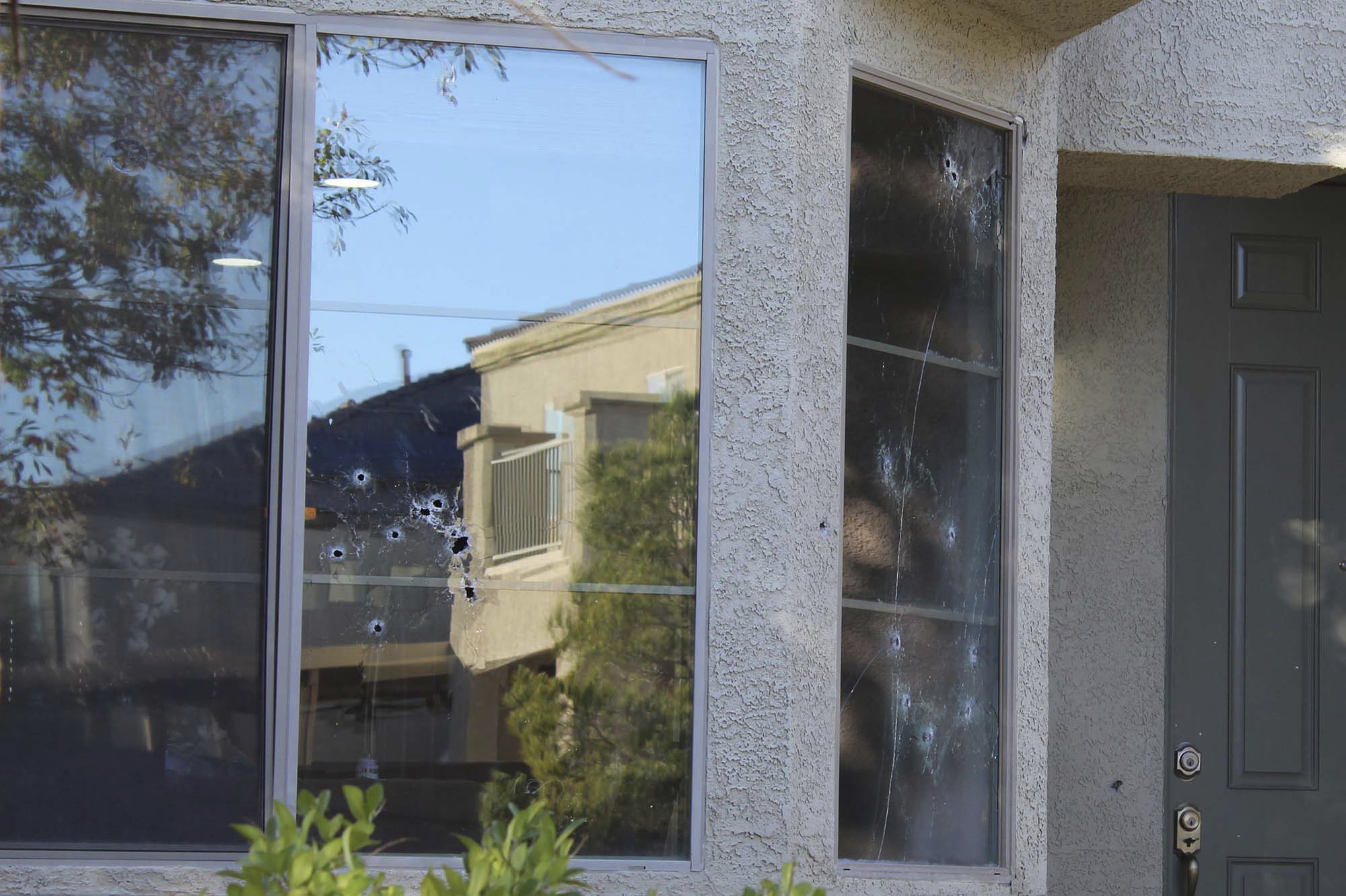 Bullet holes mark the windows of a house that was hit by gunfire Thursday night, killing an 11-year-old girl in North Las Vegas, Friday, Nov. 2, 2018. An armed group intent on gang-related retaliation opened fire on the wrong house in suburban Las Vegas, killing the girl in her kitchen, police said Friday.