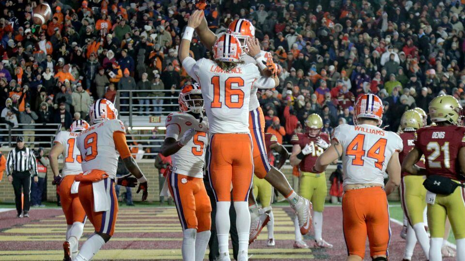 Clemson quarterback Trevor Lawrence (16) celebrates his touchdown run with teammates during Saturday's win at Boston College.