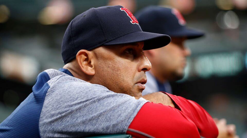 ston Red Sox manager Alex Cora leans against the dugout rail during the second inning of a July game against the Baltimore Orioles.