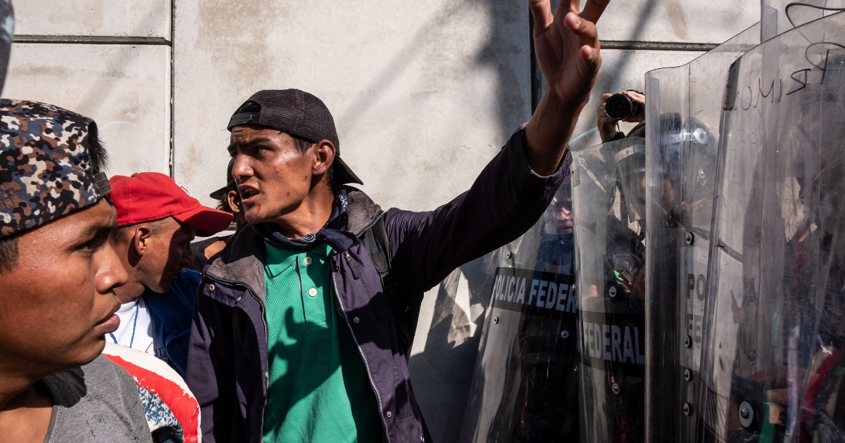 Mexican Police officers block the way to Central American migrants