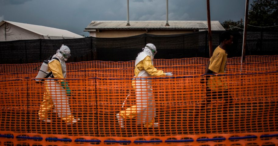 Health workers escort a Ebola patient at a Ebola treatment center.