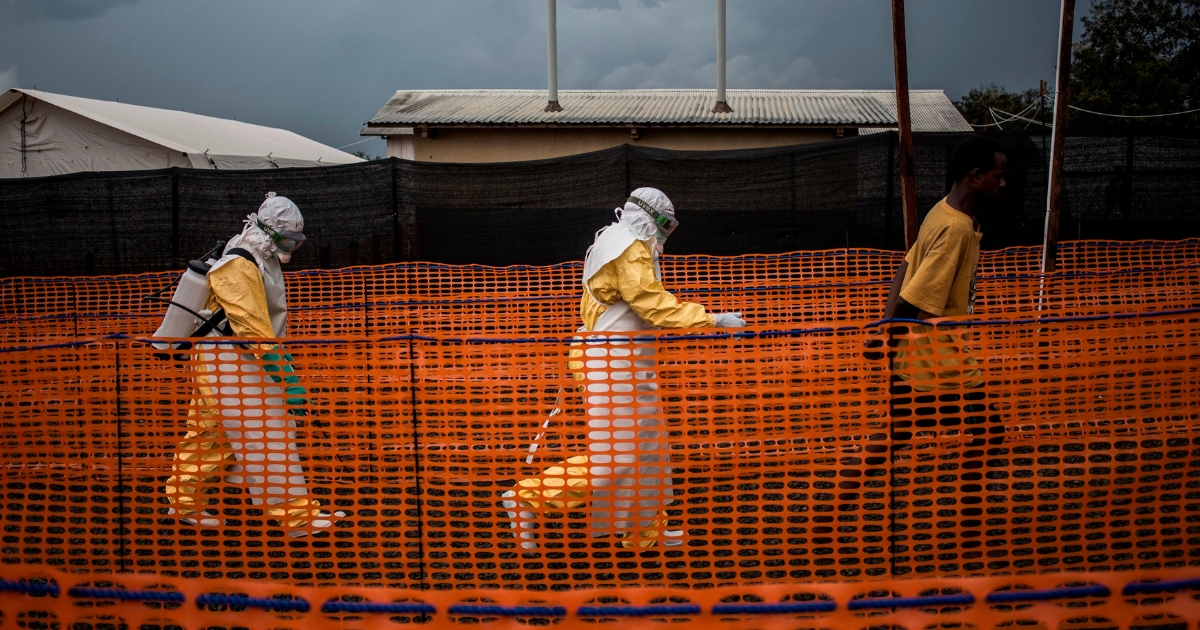 Health workers escort a Ebola patient at a Ebola treatment center.