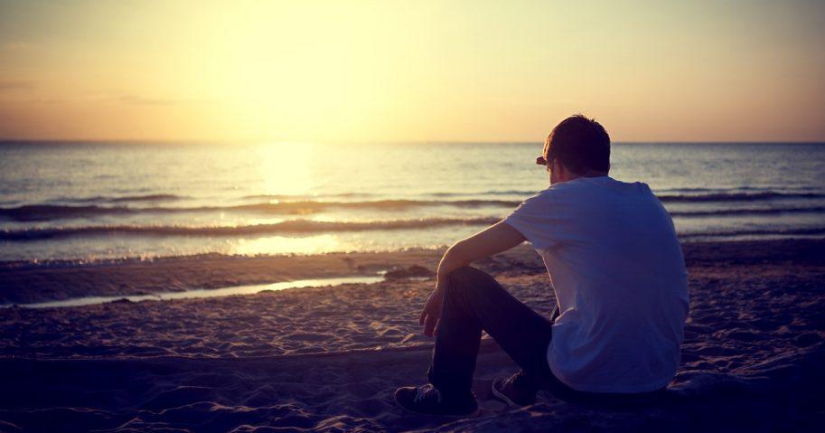 Man sitting alone on the beach.