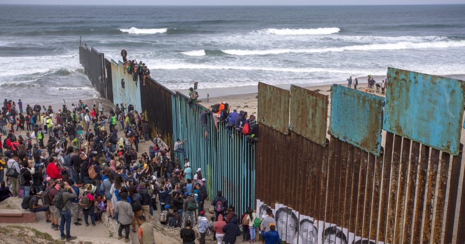 People climb a section of border fence to look into the U.S. as members of a caravan of Central American asylum seekers arrive to a rally on April 29, 2018, in Tijuana, Baja California Norte, Mexico.