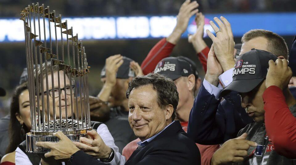 Boston Red Sox owner John Henry, partially hidden at left, and chairman Tom Werner hold the championship trophy beside manager Alex Cora, right, after Game 5 of baseball's World Series against the Los Angeles Dodgers in Los Angeles on Oct. 28, 2018.