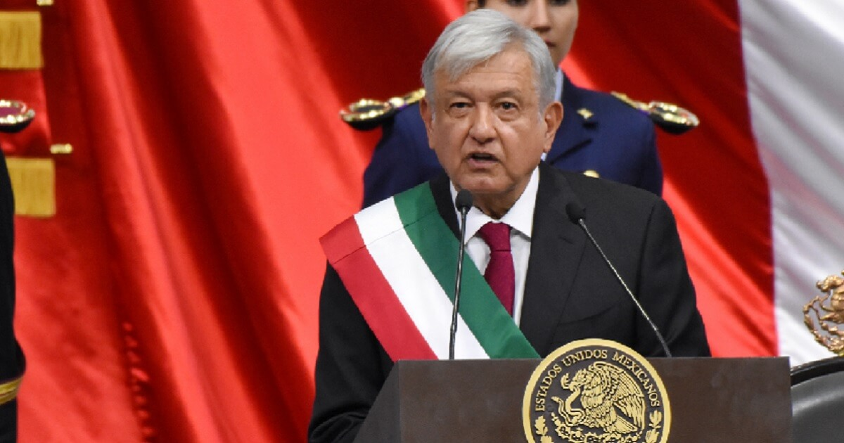 Andres Manuel Lopez Obrador wearing a sash in Mexico's national colors of green, white and red.