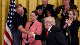 US President Donald Trump shakes the hand of Nebraska State Trooper Sam Mortensen during an event on a year of progress and action to combat the opioid crisis.