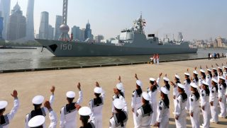 Chinese sailors wave off a Chinese naval ship as it leaves Shanghai.