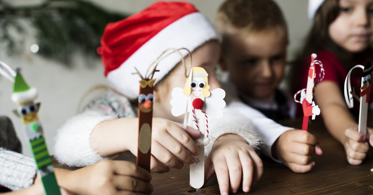 Young children holding popsicle sticks decorated for Christmas.