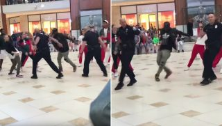 A pair of police officers dancing with a group in a mall.