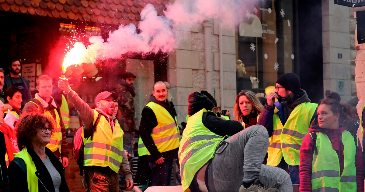 Demonstrators wearing yellow vests gather during a visit by French Foreign Minister Jean-Yves Le Drian in Biarritz, southwestern France on Dec. 18, 2018.