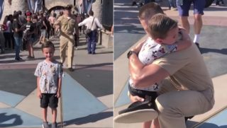 A military dad sneaks up behind his son who is taking a picture in front of the Disneyland castle.