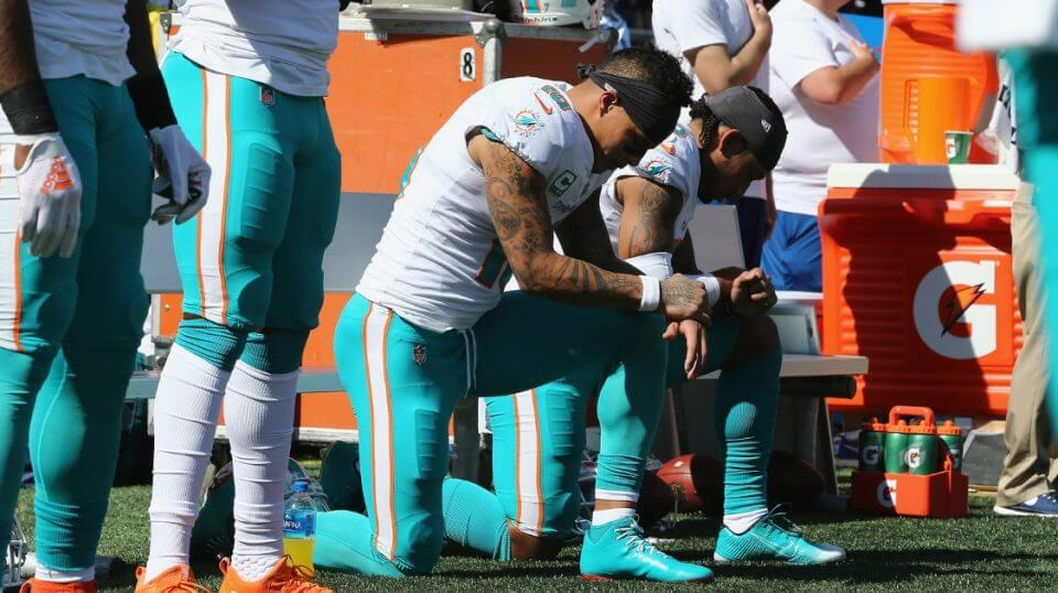 Kenny Stills, left, and Albert Wilson of the Miami Dolphins kneel during the national anthem prior to their game against the New England Patriots at Gillette Stadium on Sept. 30.