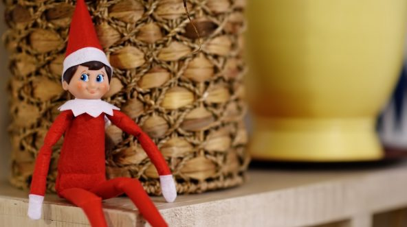 A toy elf sits on a shelf.