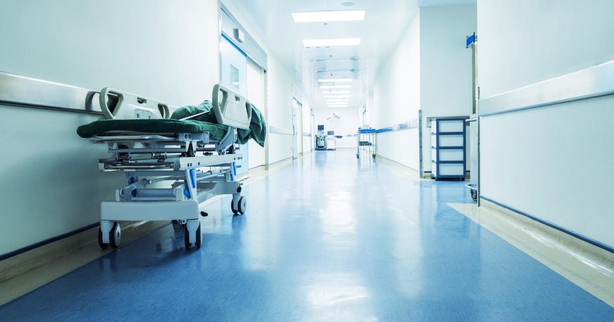 A gurney sits in an empty hospital hallway.