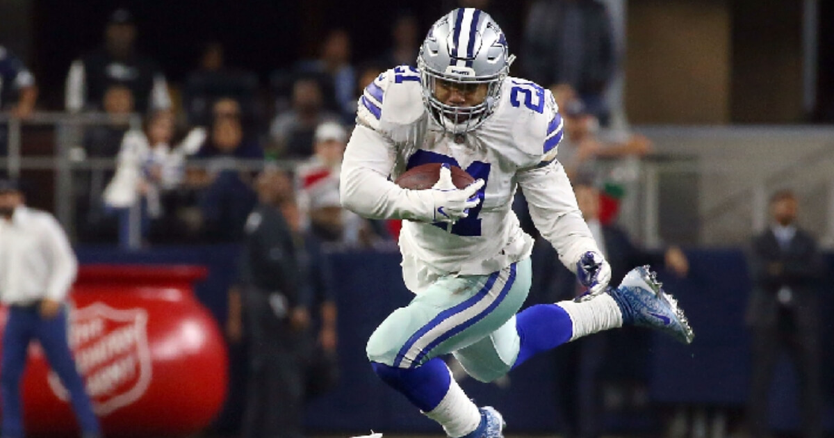 Ezekiel Elliott of the Dallas Cowboys carries the ball in the fourth quarter at AT&T Stadium on December 09, 2018 in Arlington, Texas.