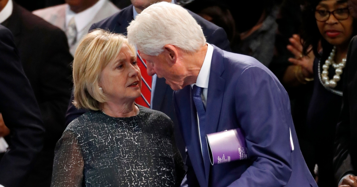 Former President Bill Clinton and wife Hillary Clinton, left, talk during the funeral service for Aretha Franklin at Greater Grace Temple, Aug. 31, 2018, in Detroit.