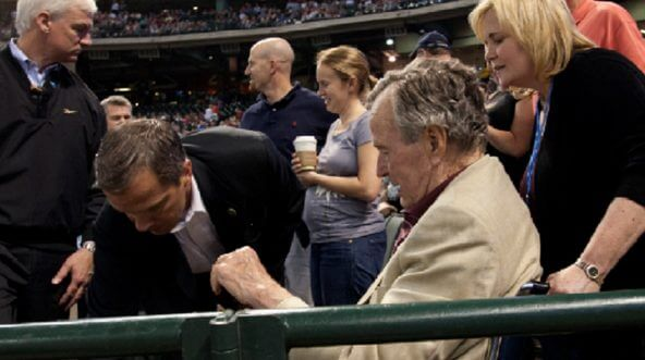 Former President George H.W. Bush is assisted by a Secret Service agent at a Houston Astros game at Minute Maid Park in Houston in 2011.
