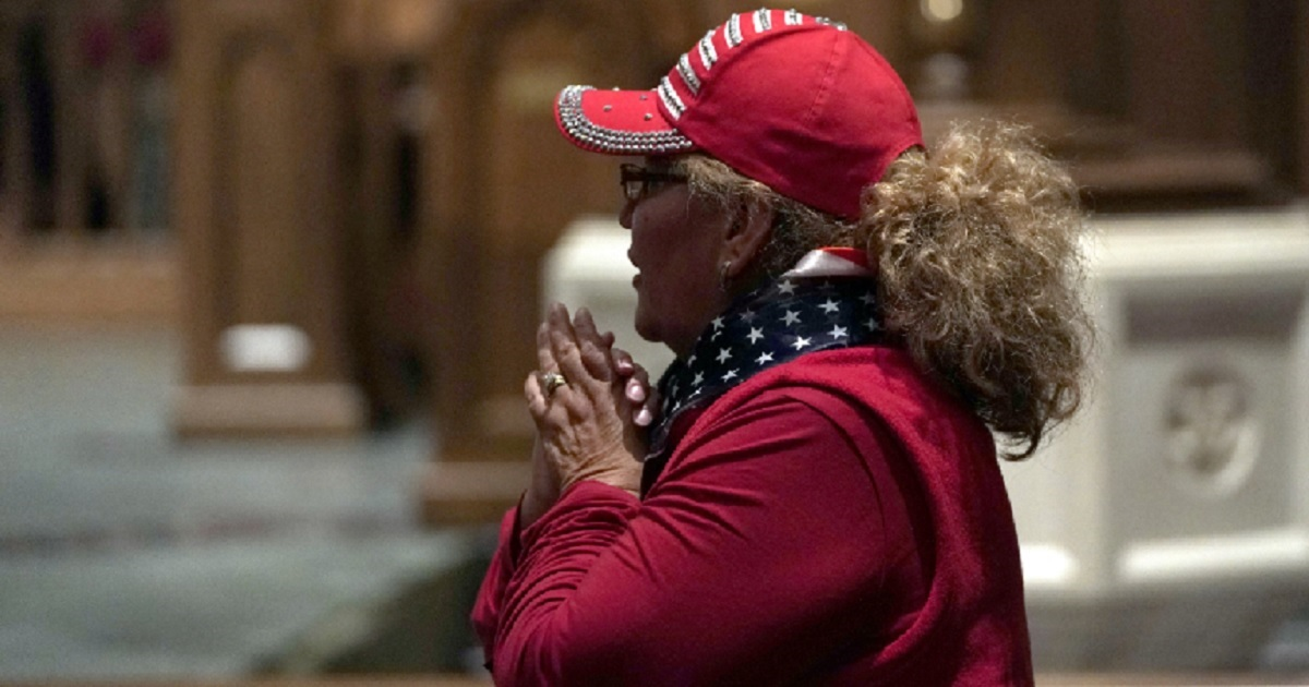 A woman clasps her hands inside Houston's St. Martin's Epicopal Church after former President George H.W. Bush's remains arrived at the church on Wednesday night.