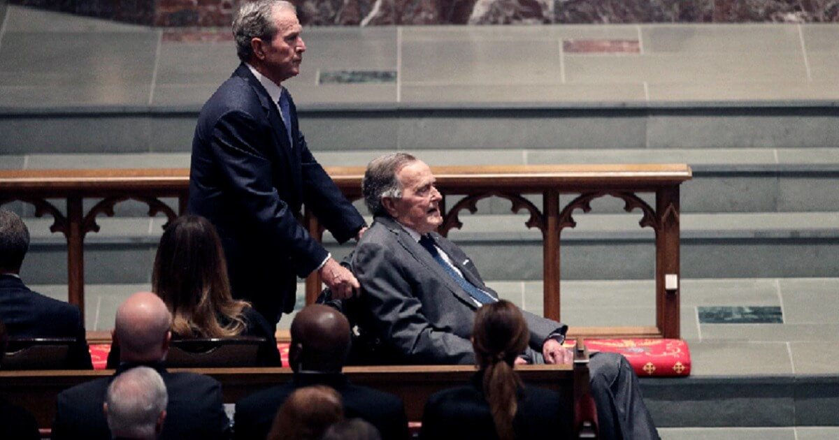 Former President George W. Bush pushes his father, former President George H.W. Bush, at the April funeral of former first lady Barbara Bush In Houston.