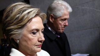 HIllary and Bill Clinton looking somber