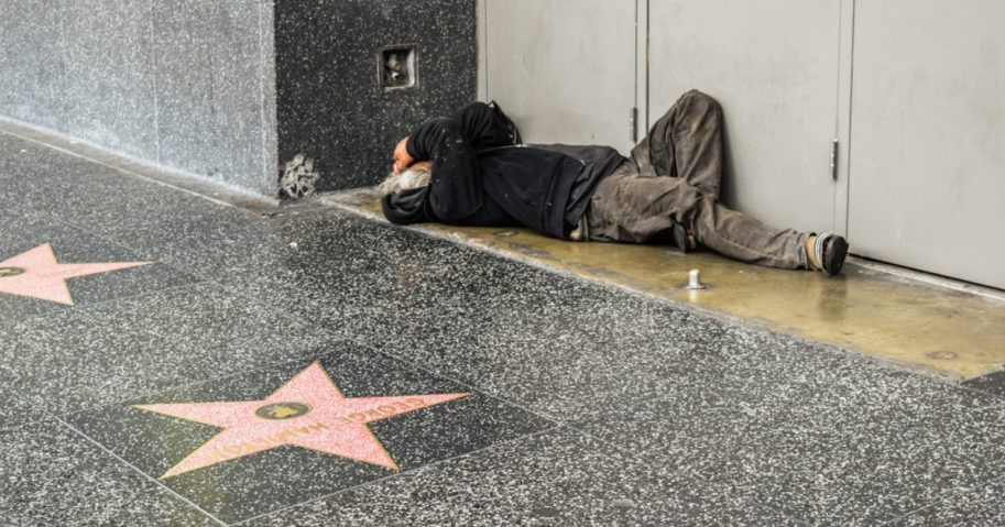 A homeless man sleeps along the Hollywood Walk of Fame in California.