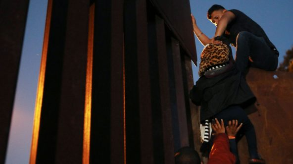 Illegal immigrants climb over the U.S.-Mexico border fence in Tijuana, Mexico, on Monday.