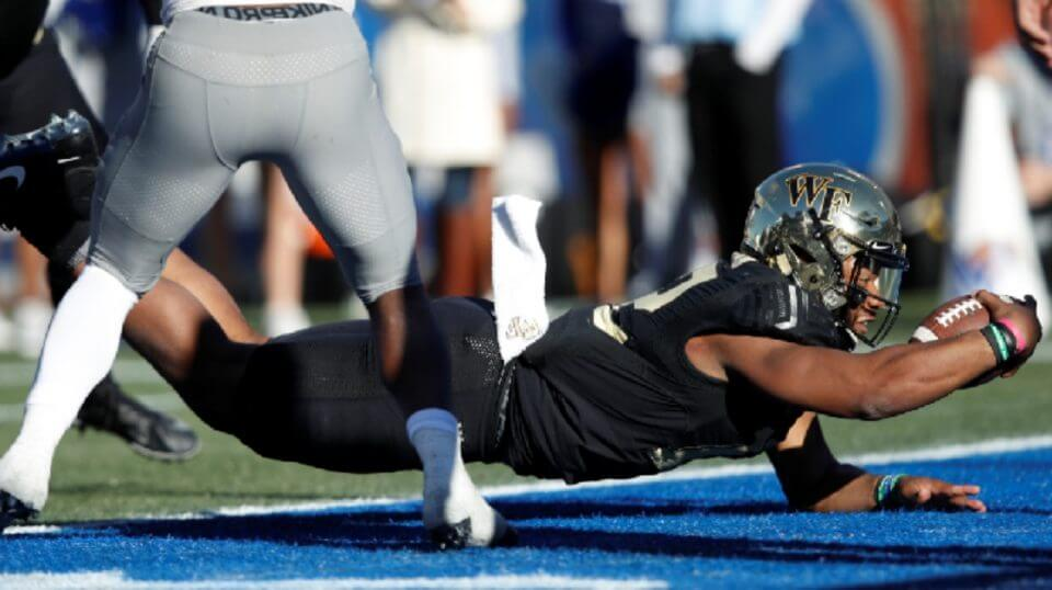 Jamie Newman #12 of the Wake Forest Demon Deacons dives into the end zone for the winning touchdown against the Memphis Tigers in the fourth quarter of the Birmingham Bowl at Legion Field on Saturday in Birmingham, Alabama.