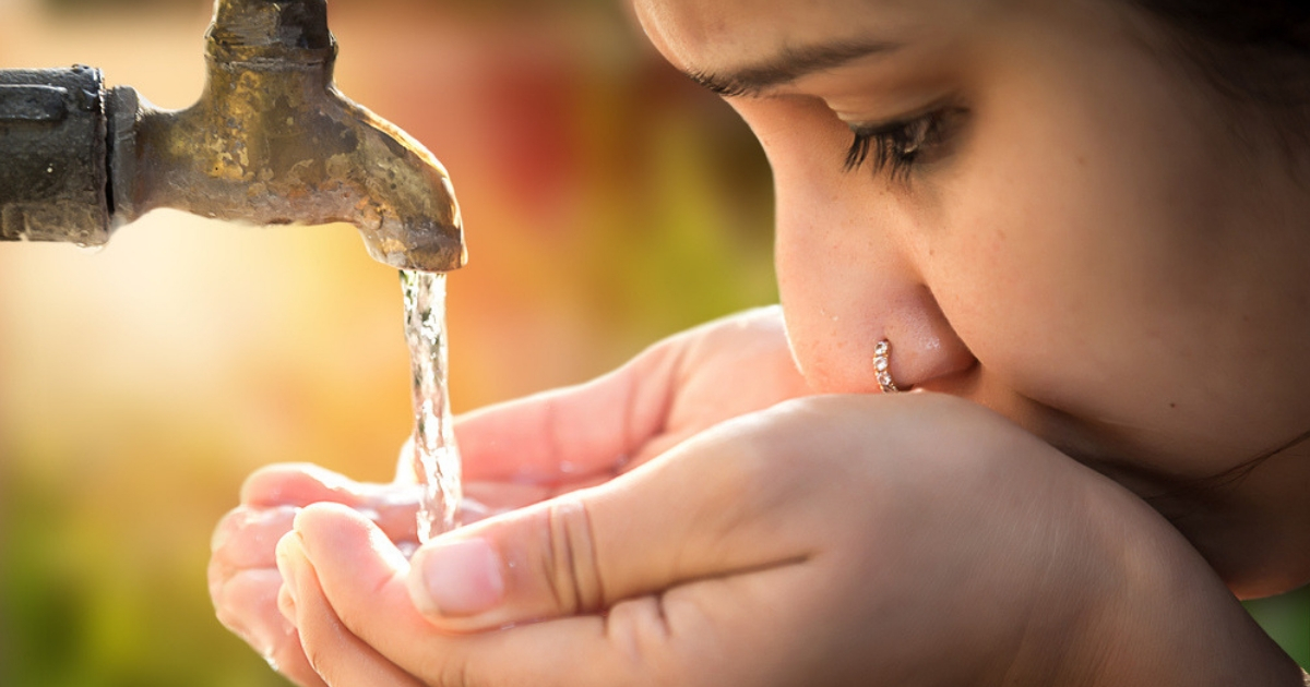 A young girl drinks water from a tap