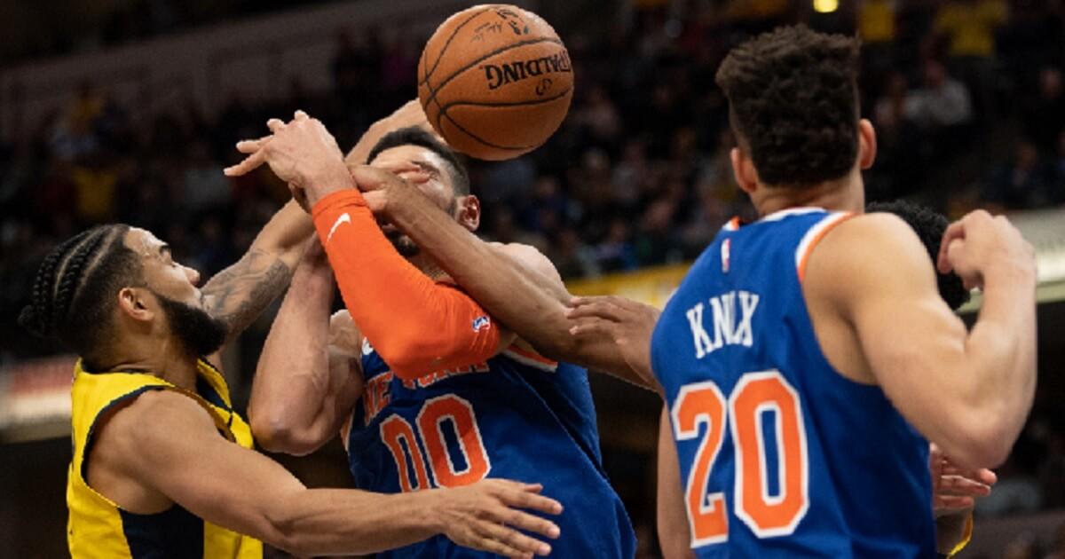 Basketball players battle for an aloft ball.