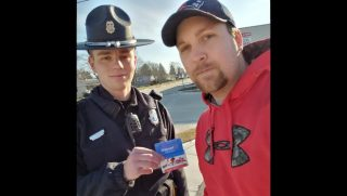 A state trooper gives a man two gift cards.