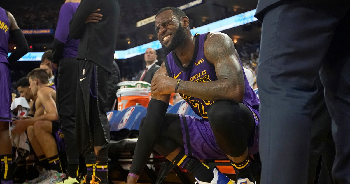 LeBron James grimaces after straining his left groin, during the second half of the team's game against the Golden State Warriors on Tuesday.