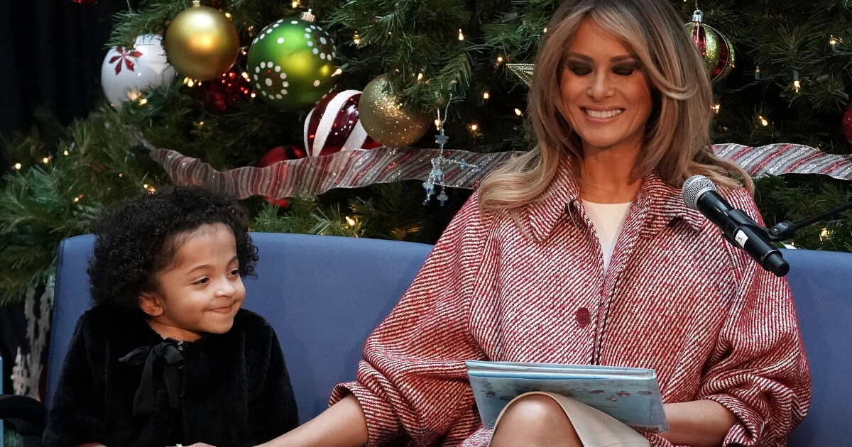 U.S. first lady Melania Trump shares a moment with patient escort Tearrianna Cooke-Starkey while reading the story 'Oliver the Ornament' during a visit to the Children's National Hospital Dec. 13, 2018, in Washington, D.C.