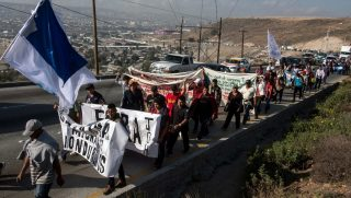 A group of Central American migrants take part in a demonstration march Tuesday in Tijuana, Mexico, heading to the U.S. Consulate to deliver a petition.