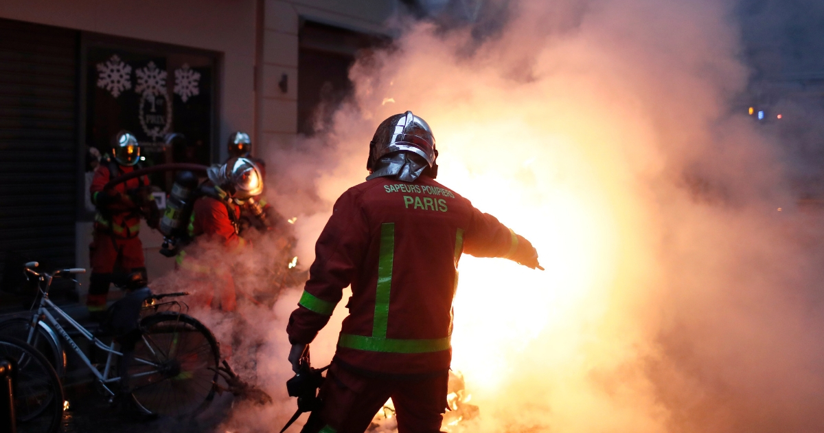 Firefighters try to extinguished a car set on fire by demonstrators during clashes with riot police, in Paris, France, Dec. 8, 2018.