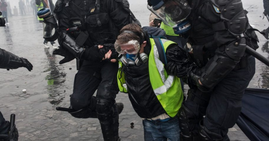 Riot police arrest a protester in Paris on Saturday.