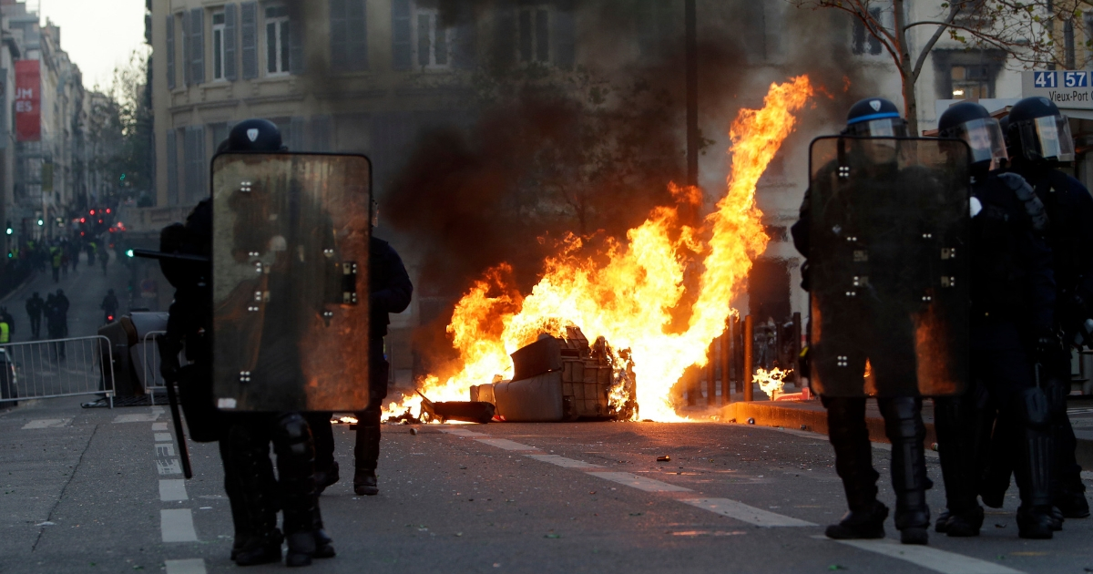 Riot police officers stand in front a burning trash bin during clashes, Dec. 8, 2018 in Marseille, southern France.
