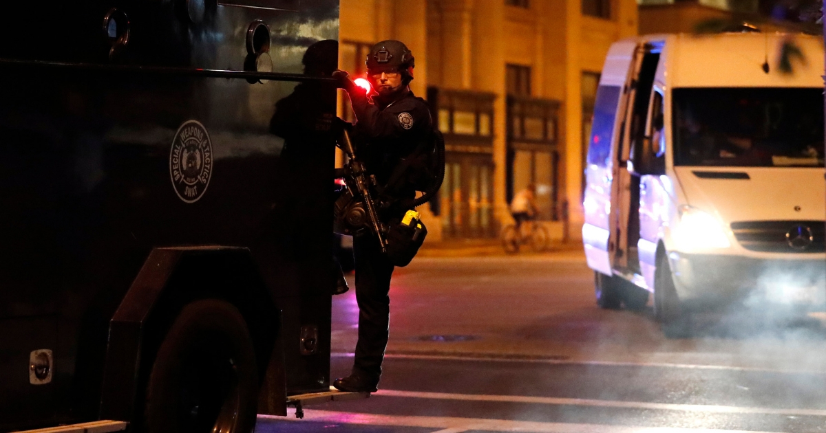 A police SWAT member rides on an armored personnel carrier.
