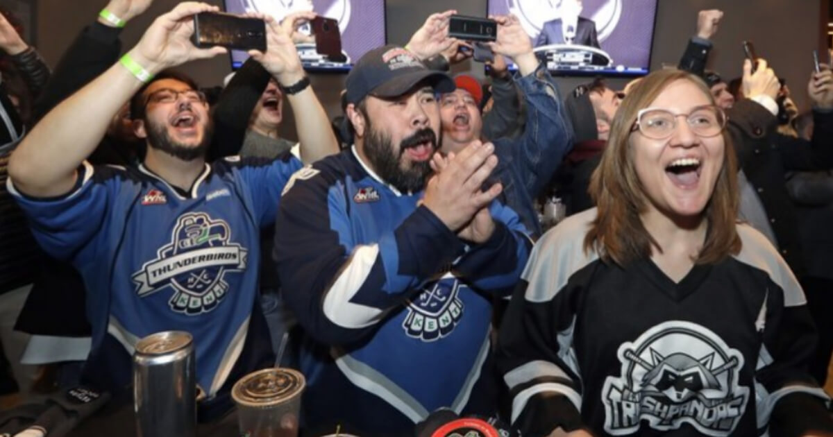 Fans in Seattle cheer the announcement of a new NHL hockey team for the city at a celebratory party