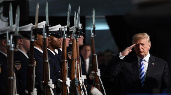 Trump salutes line of Coast Guardsmen presenting arms.