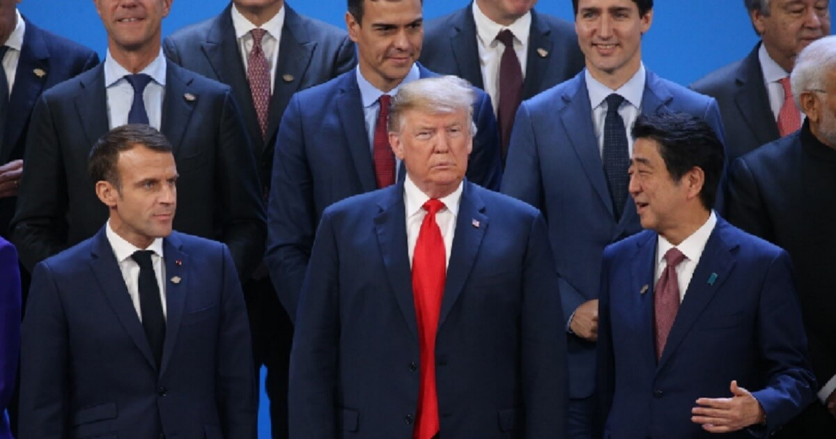 President Donald Trump stands between French Preisident Emmanuel Macron, left, and Japanese Prime Minister Shinzo Abe on Friday during a group picture shoot at the G-20 economic summit in Buenos Aries, Argentina.