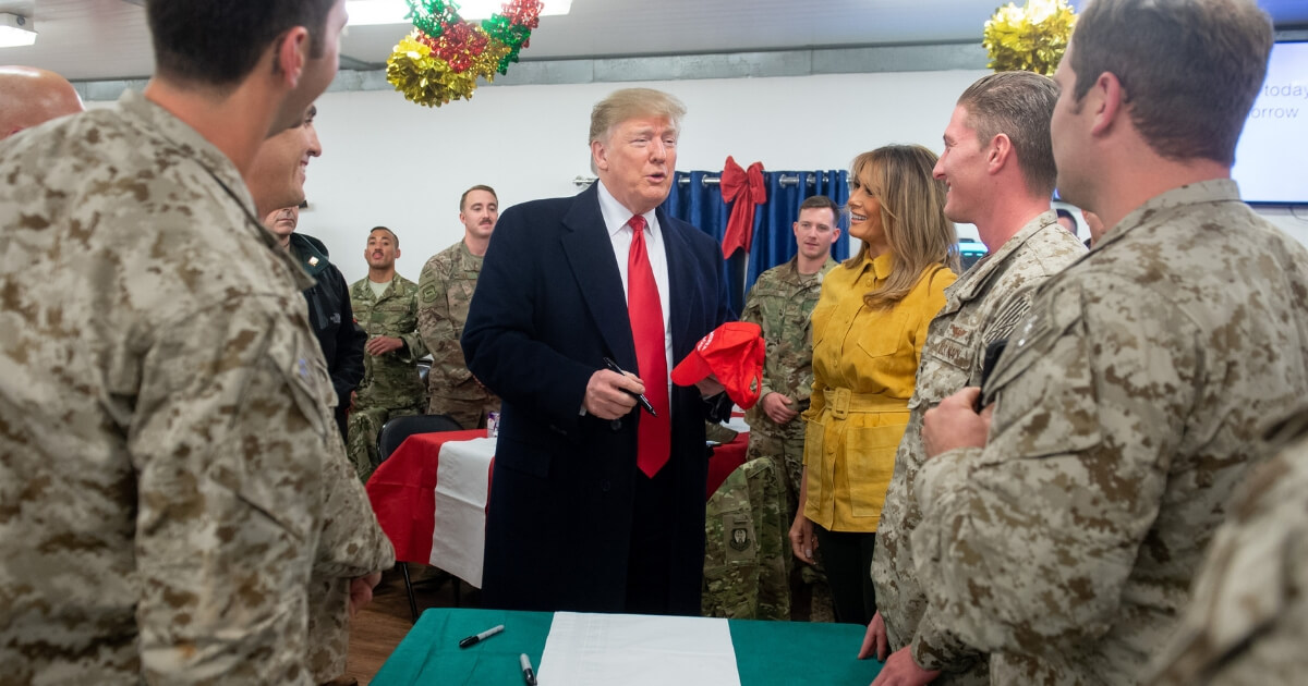 """President Donald Trump prepares to sign a """"Make America Great Again"""" hat as he and first lady Melania Trump greet members of the U.S. military during an unannounced trip to al-Asad Airbase in Iraq on Wednesday."""