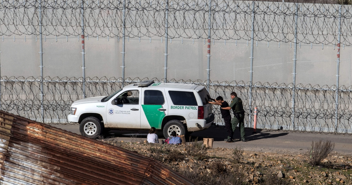 Central American migrants -traveling in a caravan- are taken into custody after crossing the Mexico-US border fence to San Diego County, as seen from Tijuana, Baja California state, Mexico, on Dec. 15, 2018.