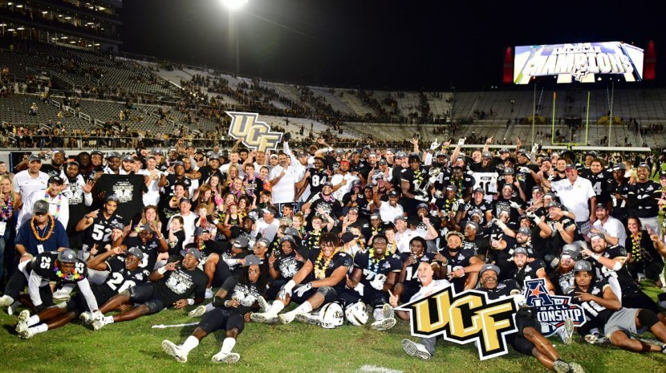 The UCF Knights celebrate with the American Athletic Conference trophy after defeating the Memphis Tigers 56-41 in the American Athletic Championship on Saturday at Spectrum Stadium in Orlando.