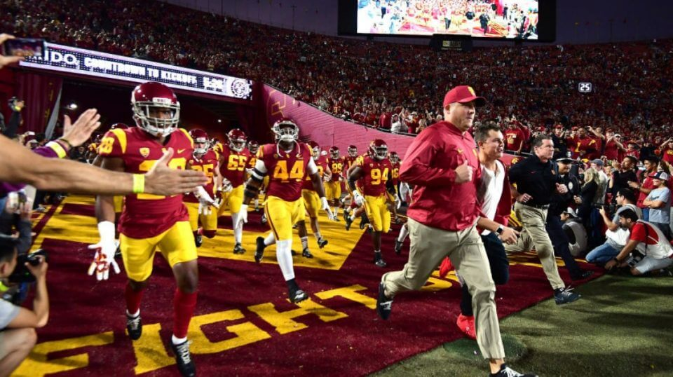 Coach Clay Helton leads the USC Trojans onto the field at the Los Angeles Memorial Coliseum.