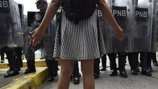 A Venezuelan college student stands in front of a line of riot police Nov. 21 during protests in Caracas.