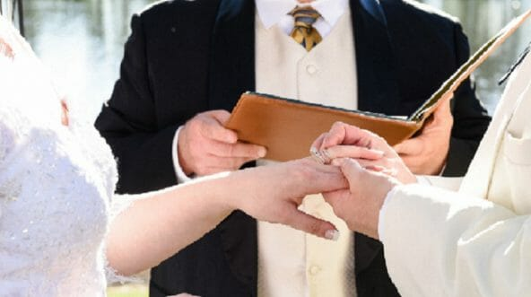 A groom puts a ring on a bride's finger.