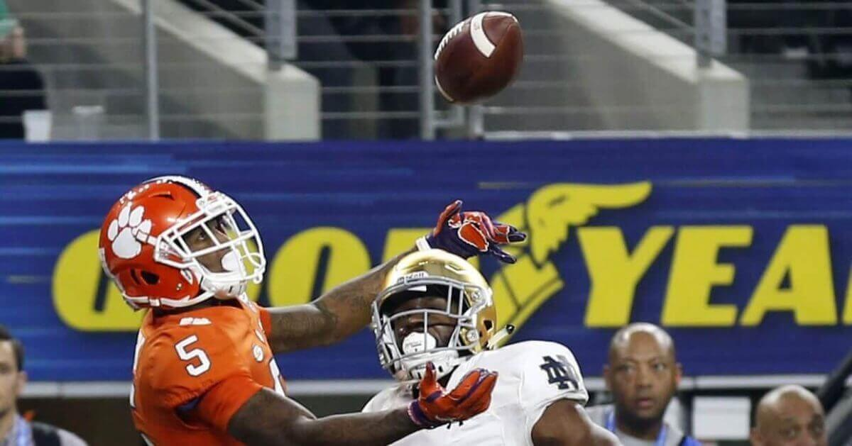 Clemson wide receiver Tee Higgins (5) reaches up to catch a ball that was tipped by Notre Dame cornerback Donte Vaughn (8) in the end zone for a touchdown late in the first half of the NCAA Cotton Bowl semi-final playoff football game on Saturday in Arlington, Texas.